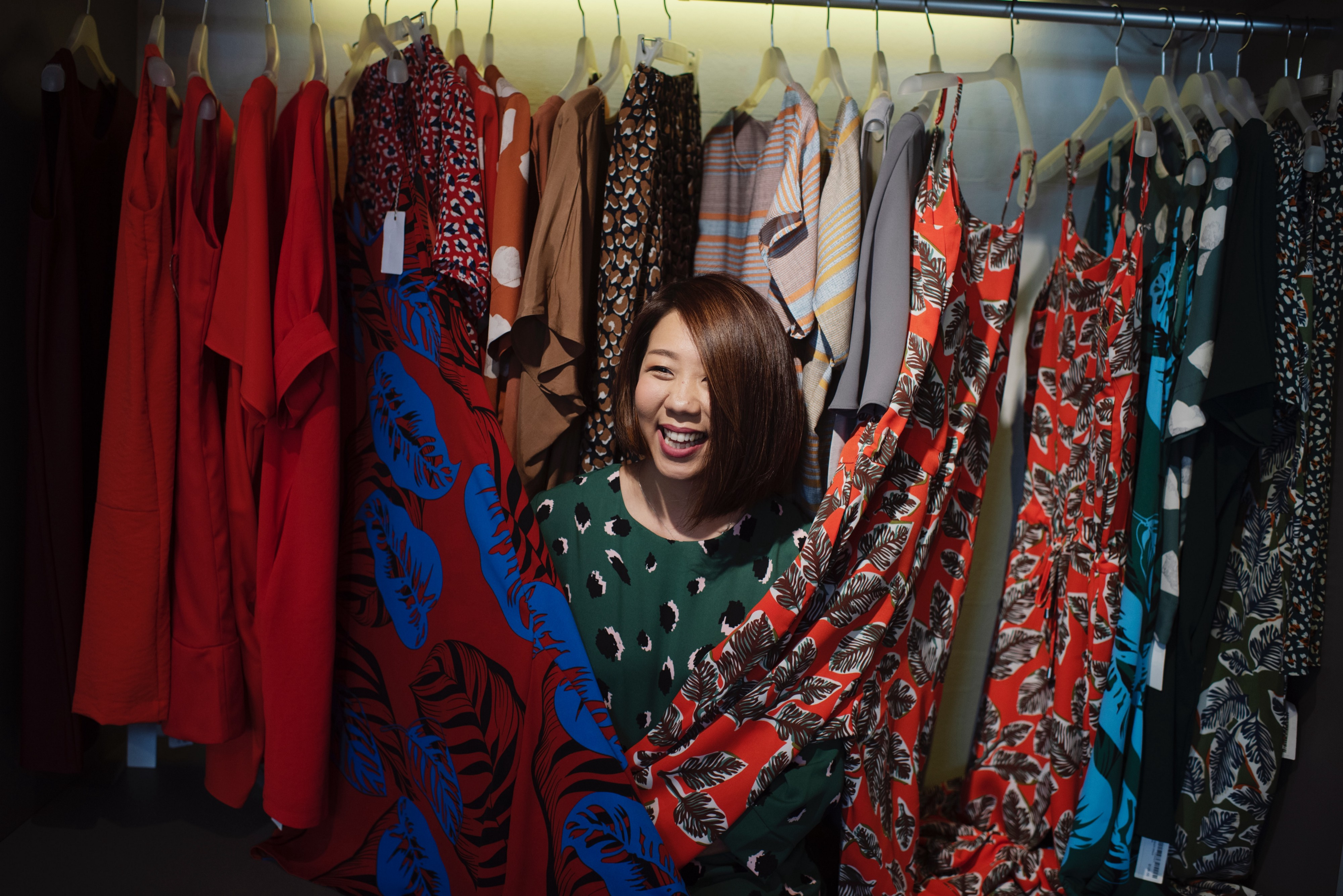 Person, probably an Asian woman, smiles among a rack full of dresses.