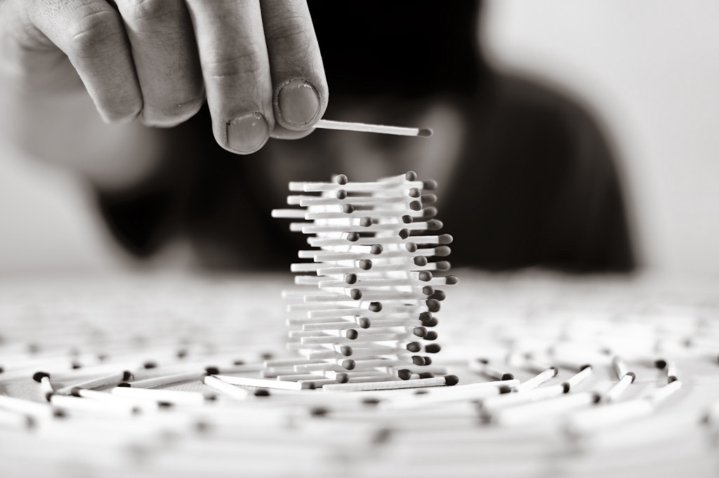 A black and white photo of cigarette sticks stacked together like Jenga.